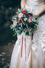 The ruched oyster satin of a vintage wedding gown is contrasted with a bouquet of cream and red roses and silvery greenery