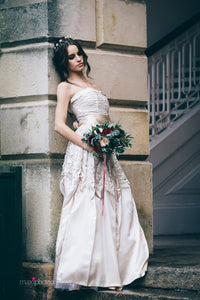 A dark haired model in a vintage gown leans against the wall of a historic building. She wears an oyster satin 1950's strapless dress with a ruched bodice and folded collar. She carries a bouquet of cream, pink and deep red flowers