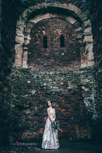 The ivy covered walls of Exeter castle loom above a bride in an oyster satin 1950's vintage wedding dress. The original vintage 50's dress has ruching and a bell skirt