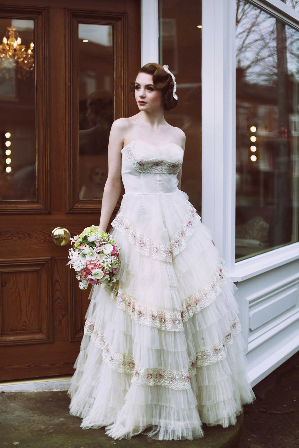 a fifties bride leans against a doorway wearing a dress made with tiers of white lace edged with a pretty pink rosebud pattern. A pink and white bouquet rests in her hand, and an elegant 50's fascinator graces her head.