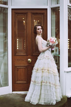 A vintage bride in a strapless lace gown with a boned bodice and full length frilled lace skirt