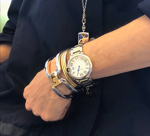 Monica wearing our Two-Tone Statement Cuff, Flex Cuff, and Rectangular Locket layered with her Cartier watch.