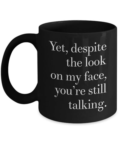 Image of Yet despite the look on my face you're still talking. Fun black ceramic mug. Great coffee or tea mug full of sarcasm. Funny gift for anyone.