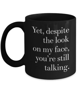 Yet despite the look on my face you're still talking. Fun black ceramic mug. Great coffee or tea mug full of sarcasm. Funny gift for anyone.