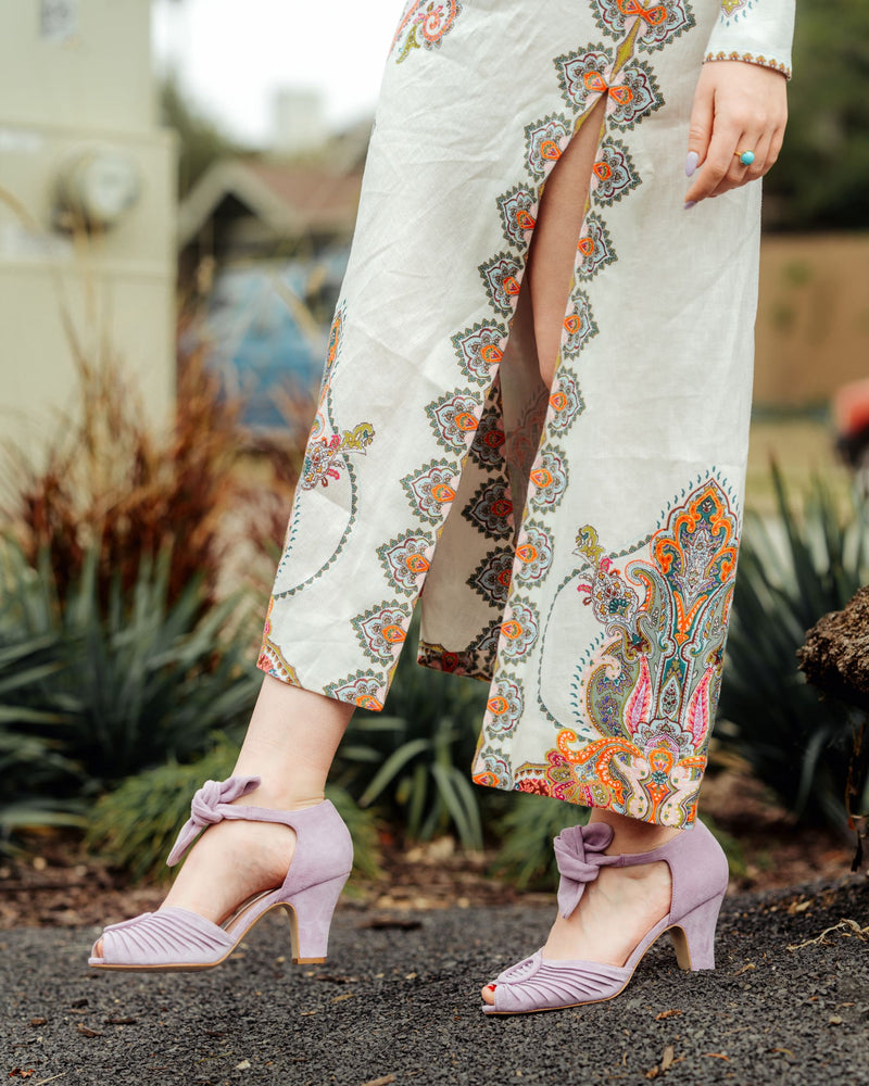 Loretta sandals in Luxe Lilac suede by Miss L Fire. Dress by Serafina. Available at The Shops at Mission Village, San Marino, California.