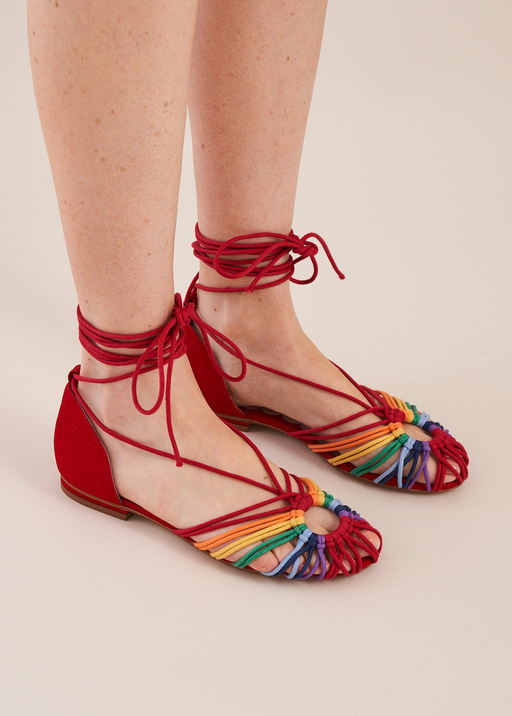 Penelope in rainbow multi is a ballet flat with a multi color cotton cord hand woven macrame upper, red leather heel counter and red cord ankle tie straps.  By Miss L Fire. Limited edition, ethically made.