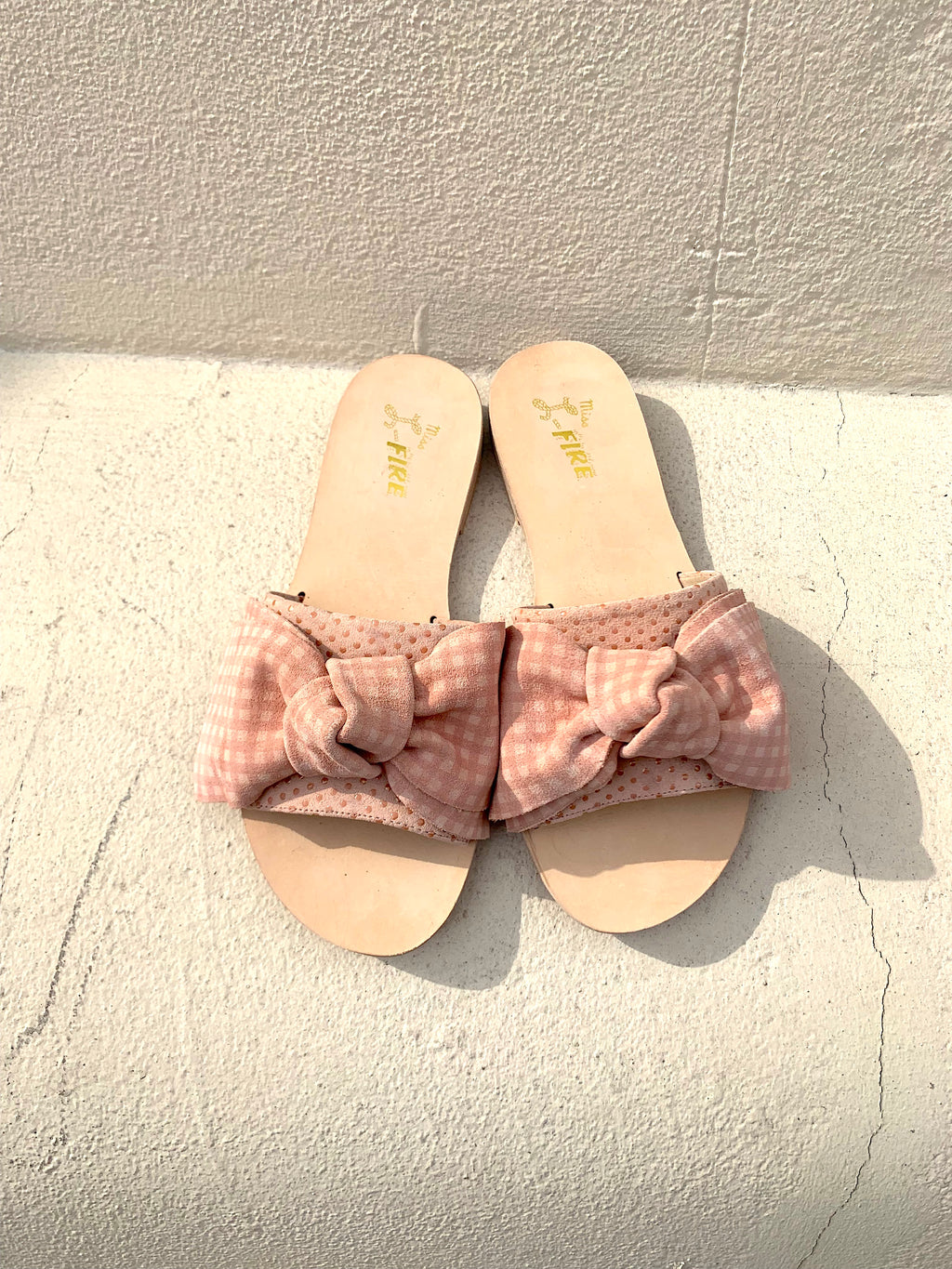 Serafina flat leather slide with bow detail in pink gingham suede. Designed in London by Miss L Fire