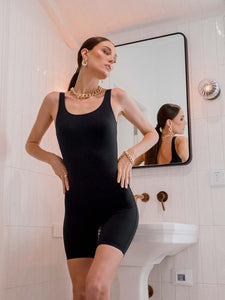 Female model wearing a black sleeveless polyamide bodysuit. The one piece has a mid thigh leg length.