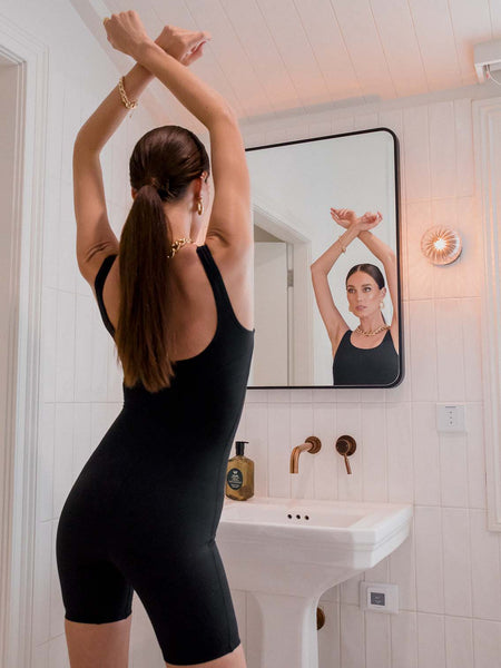 Female model wearing a black sleeveless polyamide bodysuit. The one piece has a mid thigh leg length. Model is posing in front of a bathroom mirror.