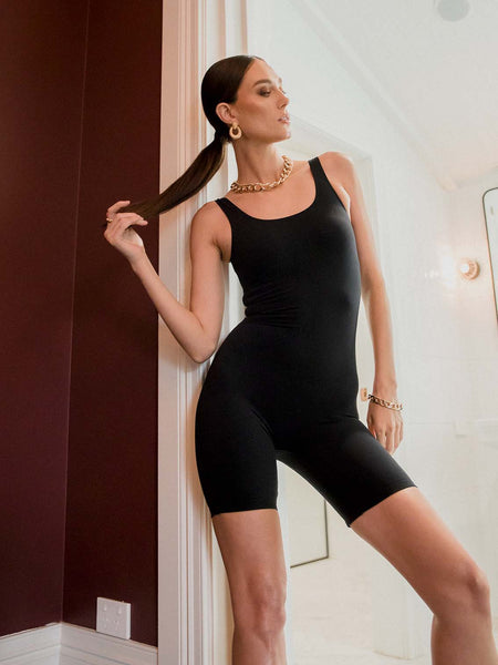 Female model wearing a black sleeveless polyamide bodysuit. The one piece has a mid thigh leg length. Model is posing in a hotel room