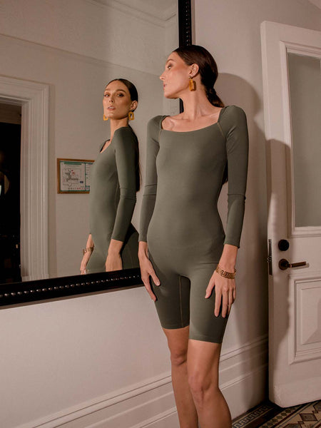 Photo of female model wearing an olive coloured green bodysuit with a square neckline, long sleeves and knee length. She is posing in front of a mirror