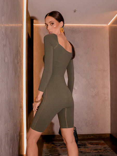 Photo of female model wearing an olive coloured green bodysuit with a square neckline, long sleeves and knee length. She is posing in a hotel to show the back of the one piece