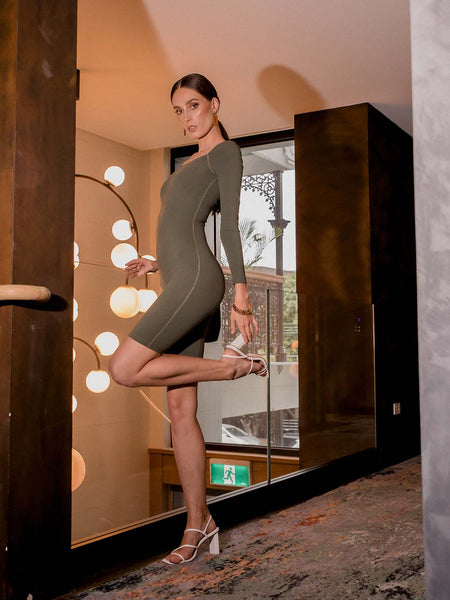 Photo of female model wearing an olive coloured green bodysuit with a square neckline, long sleeves and knee length. She is posing in a hotel to show the side of the one piece