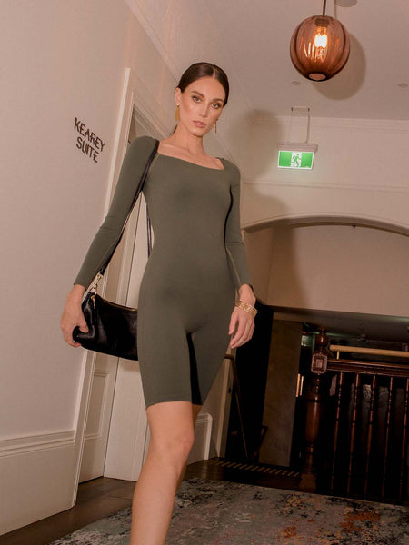 Photo of female model wearing an olive coloured green bodysuit with a square neckline, long sleeves and knee length. She is posing in a hotel with purse and accessories