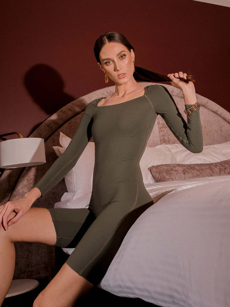 Photo of female model wearing an olive coloured green bodysuit with a square neckline, long sleeves and knee length. She is posing on a bed to show the front and side of the one piece