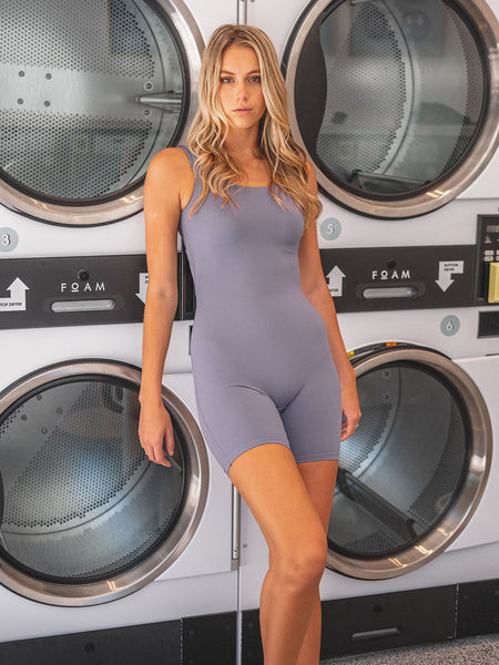Female model wearing purple sleeveless bodysuit with mid thigh leg length