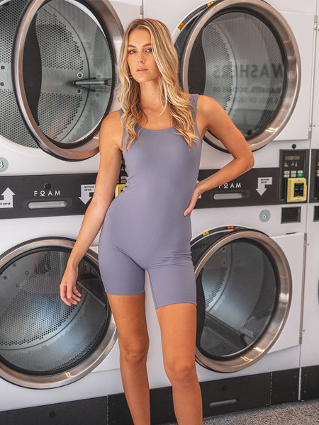 Blonde female model wearing purple sleeveless bodysuit with mid thigh leg length