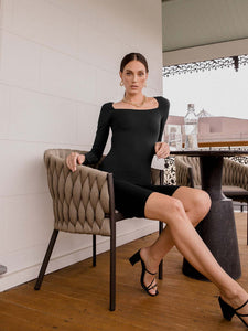 Female model wearing black long sleeve bodysuit. It has a rectangle neckline and is above knee length. Model is posing sitting on seat on a balcony