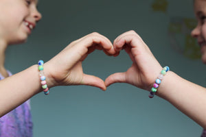 two young girls making heart with hands wearing Rainbow Anxiety crystal bracelets by MacRae Naturals