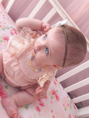 Baby girl in crib wearing Chloe baltic amber teething necklace by MacRae Naturals