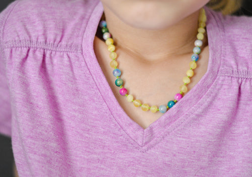 Girl wearing Baltic Amber Teething and Pain Necklace in 'Iris'