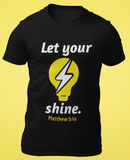 black let your light shine tshirt flatlay on yellow background