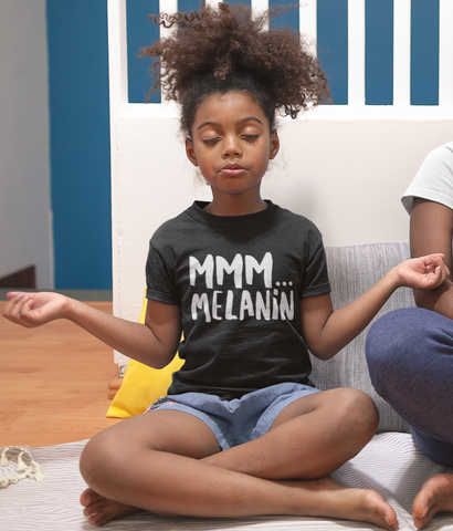 little brown girl doing yoga pose wearing black melanin tee