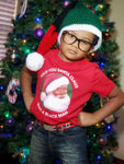 young boy standing in front of christmas tree santa hat serious expression glasses wearing red santa claus is black tshirt