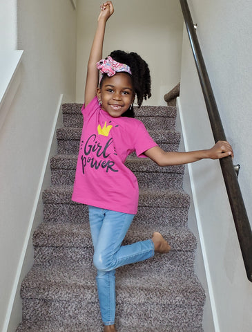 Pretty girl standing on stairs posing berry girl power tshirt crown natural hair
