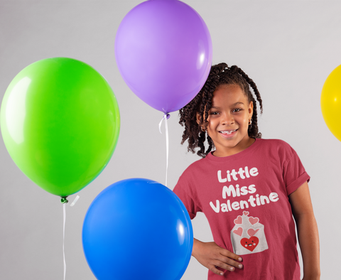 happy child smiling near balloons wearing little miss valentine tshirt