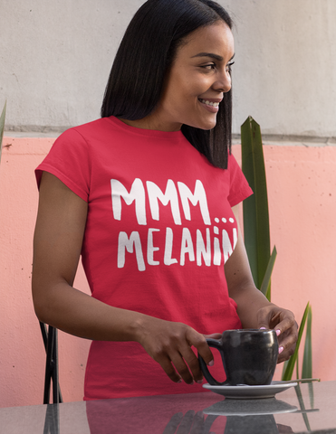 Black woman wearing red melanin tee outside with cup of tea