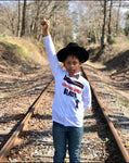 young black child standing on railroad tracks wearing unapologetically black tee shirt fist in air black and proud