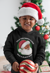 little boy wearing black santa hoodie in front of tree