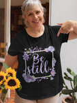 Elderly woman outdoors holding flowers wearing black be still floral tshirt