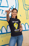 woman in front of wall throwing up peace sign wearing black let your light sine tshirt