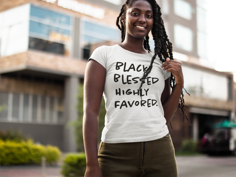 smiling black woman with braids wearing white blessed tee