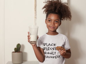 black child with natural hair wearing blessed tee holding cookie and milk