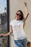 happy woman on balcony with hand in the air wearing white let go let God t shirt inspirational motivational message