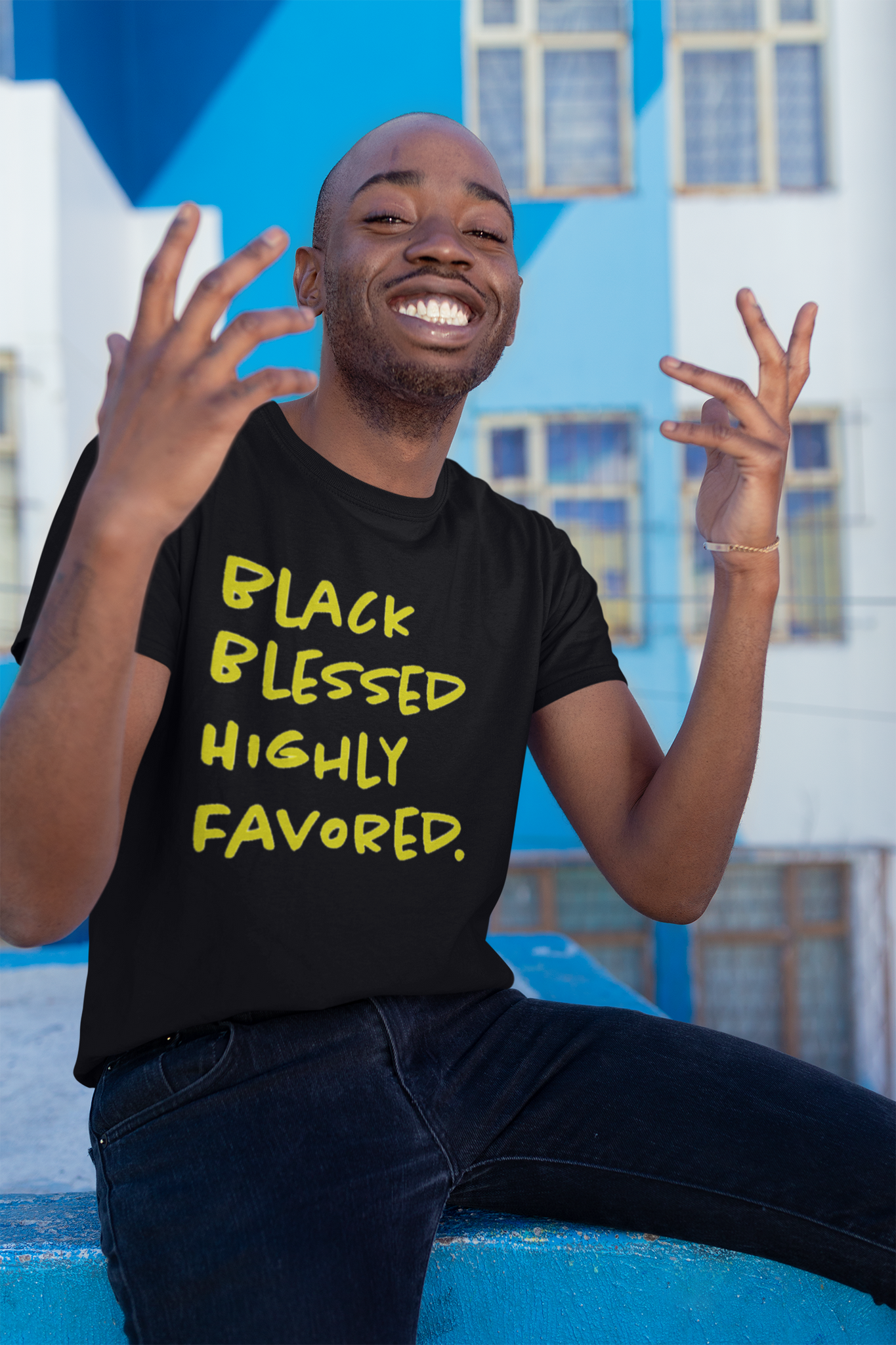 smiling black man sitting down wearing black blessed tee with hands in the air