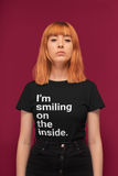 smiling on the inside black tshirt woman standing straight face