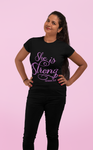 woman smiling standing near pink background with black she is strong t shirt