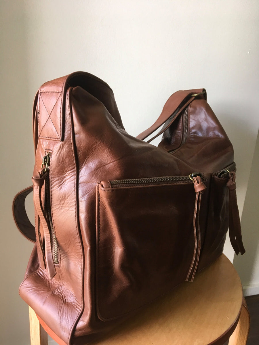 The Sender-Curved hobo style handmade leather bag.Extra wide crossbody strap