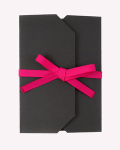Closed Wedding Bingo charcoal game package with a hot pink ribbon