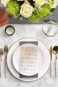 Rose gold glitter Wedding Bingo game card on a wedding place setting