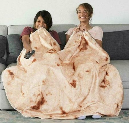 Two girls sitting on sofa with a real looking burrito blanket that looks like a tortilla shell taco, while watching TV