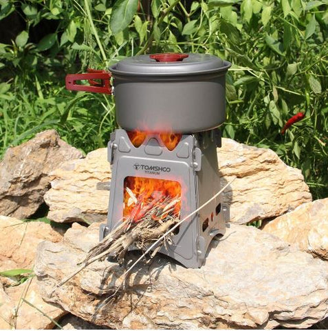 small wood burning portable camping survival stove, burning wood and has a metal pot on top with lid