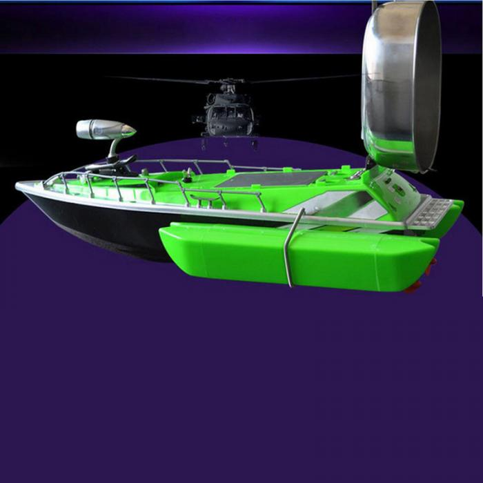 Green RC fishing boat with chum tray in up position on top to attract more fish