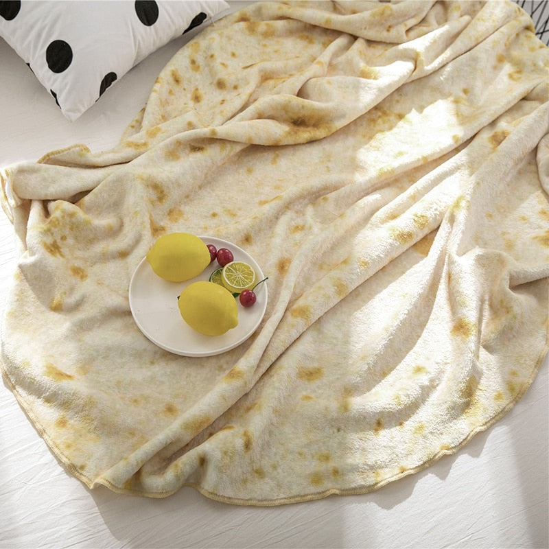Real looking burrito blanket on a bed with bowl of fruit that looks like a tortilla shell taco