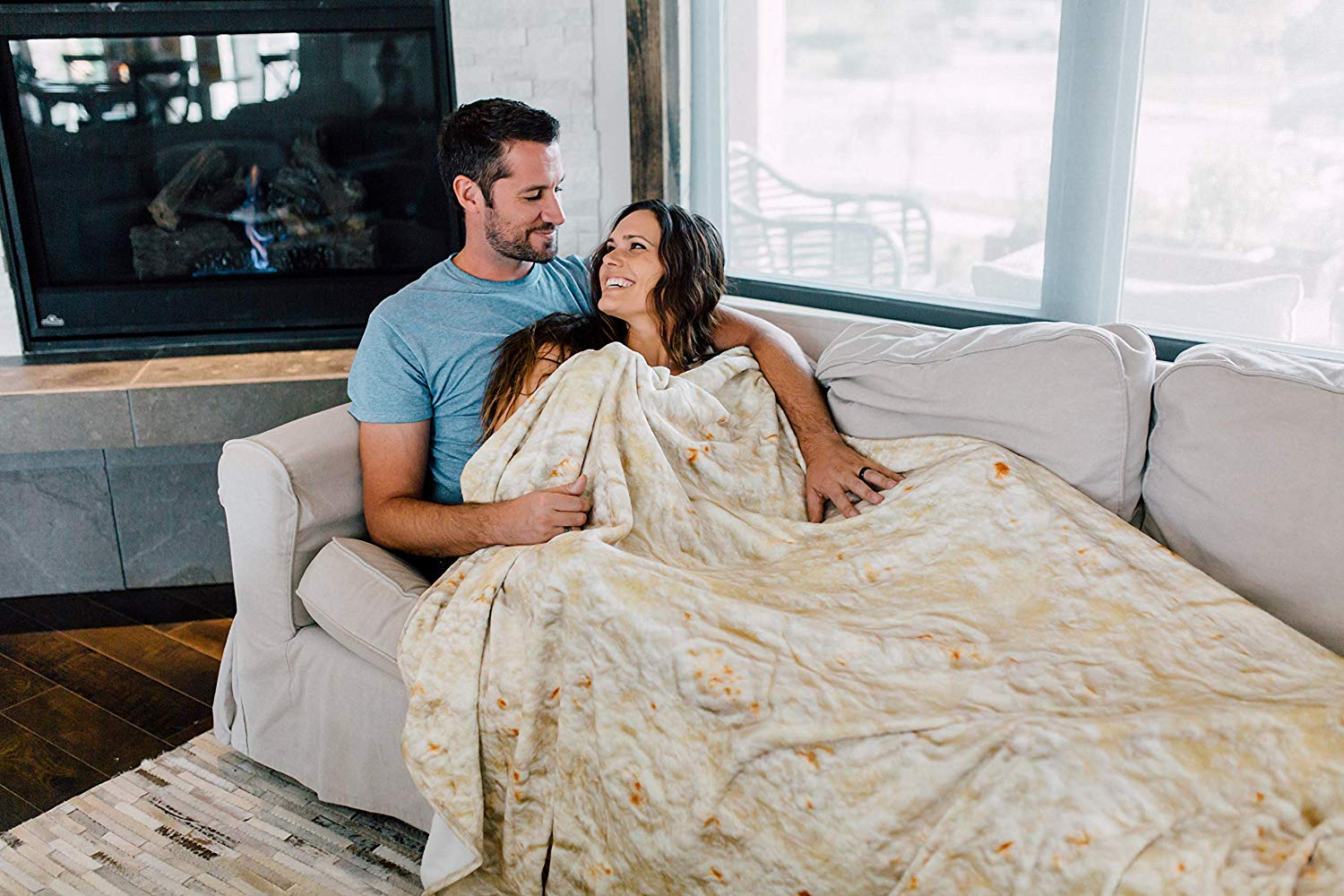 A man and a woman laying on couch with real looking burrito blanket that looks like a tortilla shell taco