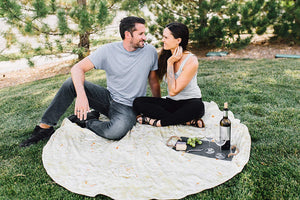 Man and a woman sitting on blanket, while on the ground with grass having a picnic with real looking burrito blanket that looks like a tortilla shell taco